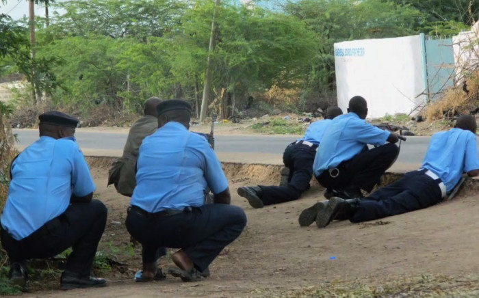 Kenyan police take cover at the Garissa University College in Kenya after gunmen attacked the school earlier today, killing at least 15 people and injuring dozens more. Picture: CNN