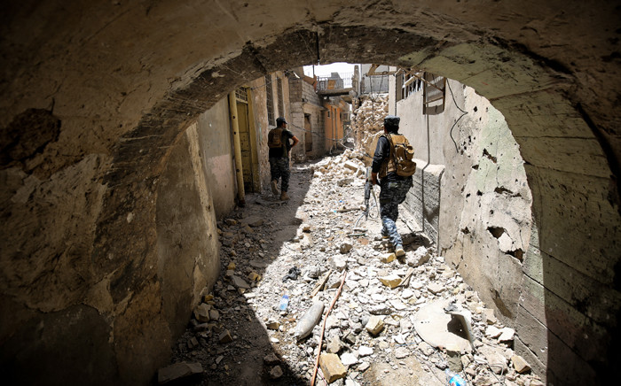 FILE: Members of the Iraqi federal police advance through the Old City of Mosul on 28 June 2017. Picture: AFP.