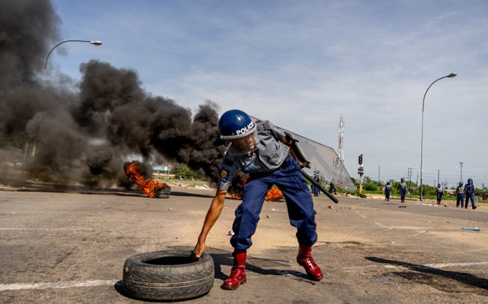 """FILE: A police officer removes tyres set by protesters during a """"stay-away"""" demonstration against the doubling of fuel prices on 14 January 2019 in Emakhandeni township, Bulawayo. Picture: AFP."""