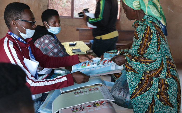 A Burundian woman receives a ballot paper from an electoral official during the presidential and general elections at the Bubu Primary school in Giheta, central Burundi, on 20 May 2020. Picture: AFP