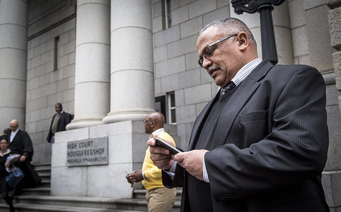 General Arno Lamoer checks his phone outside the Western Cape High Court for his pre-trial conference. Lamoer and three police officials and the Dawjee men face 109 charges between them, including fraud and corruption. Picture: Thomas Holder/EWN.