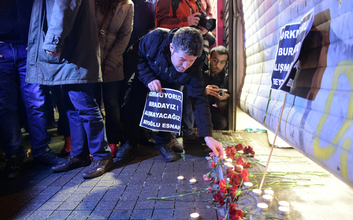 A man lights a candle at the site of a blast on Istiklal Street, a major shopping and tourist district, in central Istanbul on 19 March, 2016. Picture: AFP.