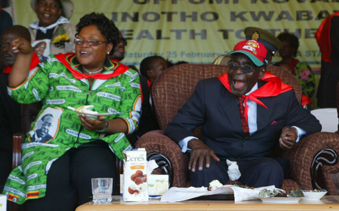 FILE: Zimbabwe's President Robert Mugabe (R) and the country's Vice President Joice Mujuru eat cake as they attend a rally marking Mugabe's 88th birthday in Mutare on 25 February, 2012. Picture: AFP.