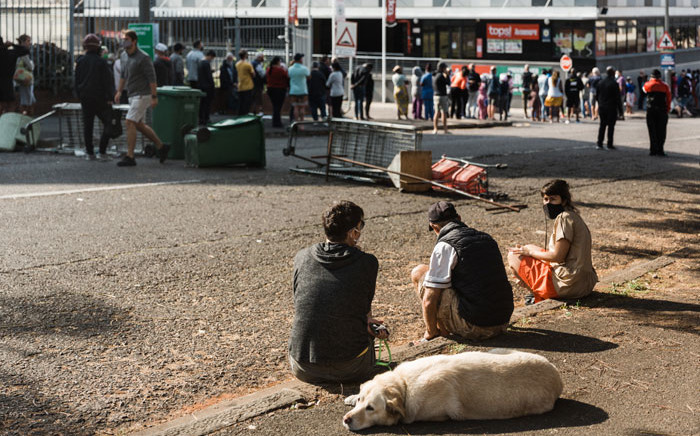People queue to enter a supermarket in Durban on 13 July 2021 as several shops, businesses and infrastructure are damaged in the city, following four nights of continued violence and looting sparked by the jailing of ex-president Jacob Zuma. Picture: RAJESH JANTILAL/AFP