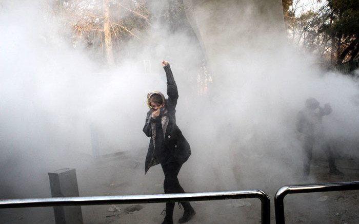 An Iranian woman raises her fist amid the smoke of tear gas at the University of Tehran during a protest driven by anger over economic problems, in the capital Tehran on 30 December, 2017.  Picture: AFP