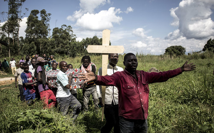 FILE: A family member of a woman killed in an alleged attack by the Ugandan Allied Democratic Forces (ADF) rebel group carries the cross for the grave on November 12, 2018, in Beni. Suspected Ugandan rebels killed six people, hacking one woman to death, and kidnapped five others in the Democratic Republic of Congo's restive east, officials said on November 11. Picture: AFP.