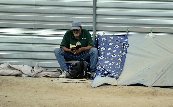 FILE: A homeless man reads next to his makeshift tent beside a street in Las Vegas. Picture: AFP