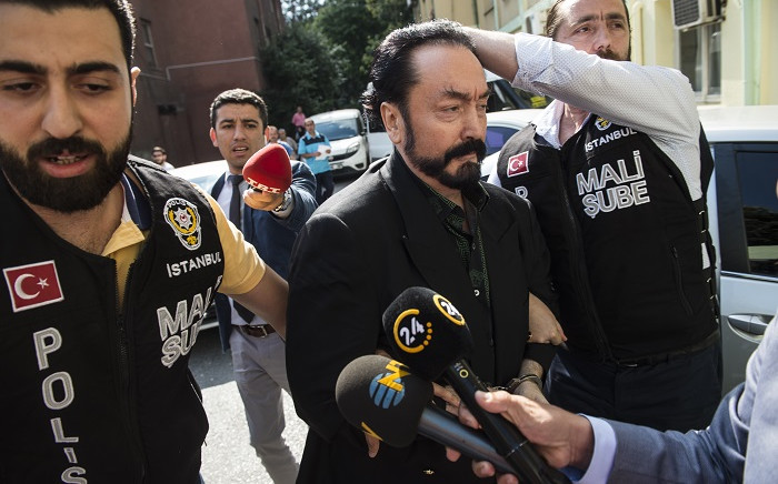 FILE: In this file photo taken on July 11, 2018 Turkish police officers escort televangelist and leader of a sect, Adnan Oktar (C) in Istanbul, as he is arrested on fraud charges. Picture: AFP