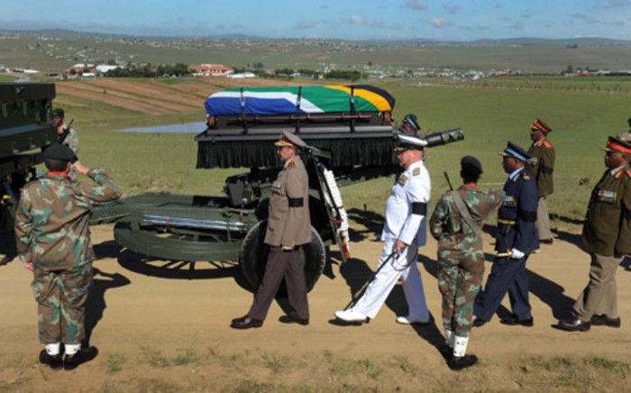 Nelson Mandela's casket is carried by police and military members during his funeral service in Qunu, 15 December 2013. Picture: GCIS.