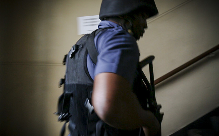 FILE: A member of the Saps Tactical Response Team makes his way up some stairs into a hostel during a raid in Bellville's CBD, Cape Town. Picture: Thomas Holder/EWN
