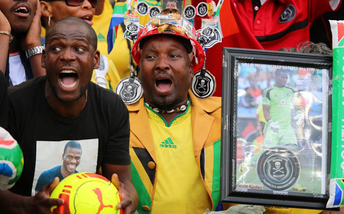 South African supporters hold a portrait of murdered Bafana Bafana captain and goalkeeper Senzo Meyiwa during the Africa Cup of Nations 2015 qualifying football match South Africa vs Sudan, at the Moses Mabhida Stadium in Durban, on November 15, 2014. AFP