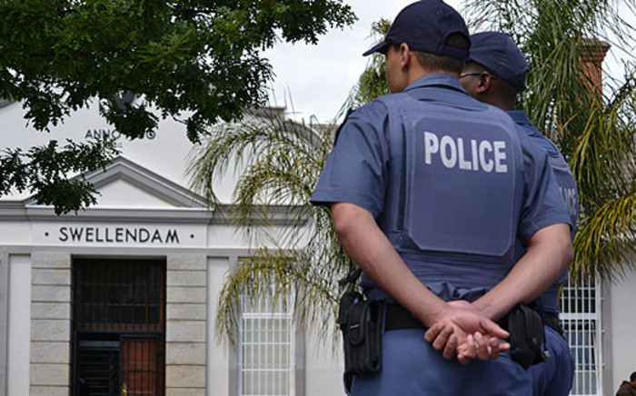 Police keep an eye during Johannes Kana's court appearance on 7 October 2013. Picture: Renee de Villiers/EWN