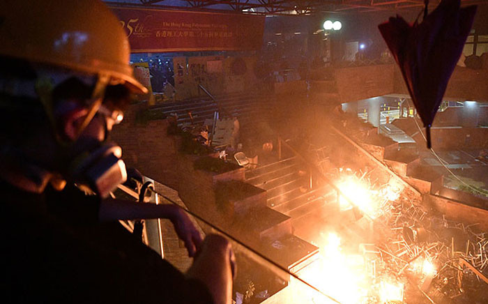An anti-government protester walks past a fire on a bridge at one of the entrance that leads into the Hong Kong Polytechnic University in the Hung Hom district of Hong Kong early on 19 November 2019. Picture: AFP