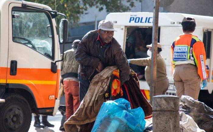 A homeless man from Doornfontein who is physically challenged struggles to lift some of his belongings which he will take to a shelter in Hillbrow. Picture: Ahmed Kajee/EWN