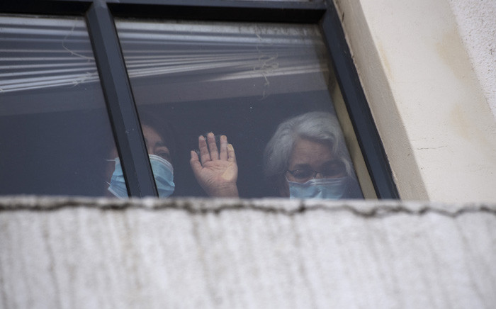 Two women in the Covid-19 ward of the Rondebosch Medical Centre join in prayers with people standing outside the building taking part in an interfaith gathering to pray for Covid patients and their carers at the Rondebosch Medical Centre, in Cape Town on January 14, 2021. Picture: Rodger Bosch/ AFP.
