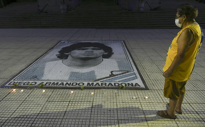 Photo released by Telam of a fan looking at candles lit next to the image of Argentinian late football legend Diego Armando Maradona at the Kirchner Cultural Center (CCK) in Buenos Aires, early on November 26, 2020. Picture: AFP