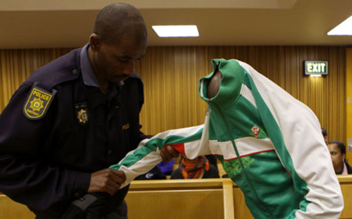 A police officer assists Xolile Mngeni, one of the men accused of murdering Anni Dewani, in the Western Cape High Court. Picture: Sapa