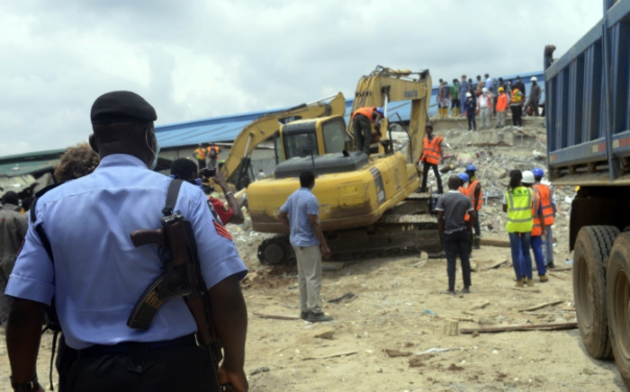 FILE: A policeman monitors the excavation of the collapsed guesthouse of the Synagogue Church of All Nations (SCOAN) in the Ikotun neighborhood of Lagos on 17 September, 2014. Picture: AFP.