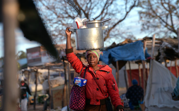 FILE: A woman carries her pots and cooking utensils to market. Picture: AFP