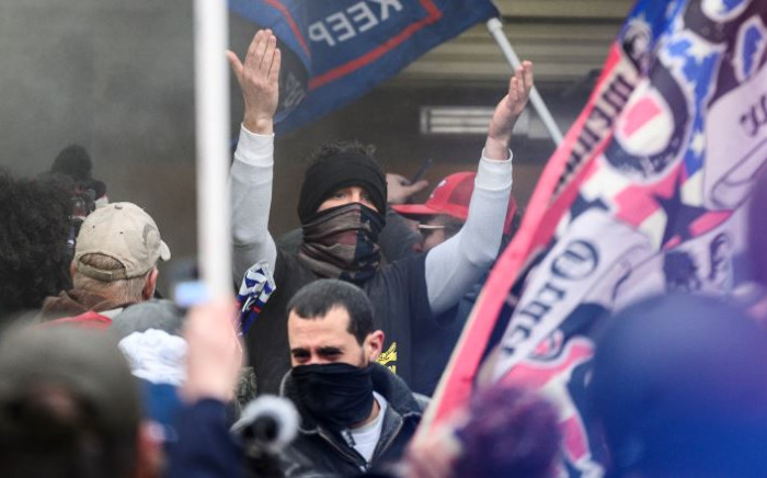 A Trump supporter gestures to other demonstrators as they try to break into the US Capitol in Washington, DC, on 6 January 2021. Donald Trump's supporters stormed a session of Congress to certify Joe Biden's election win. Picture: AFP.