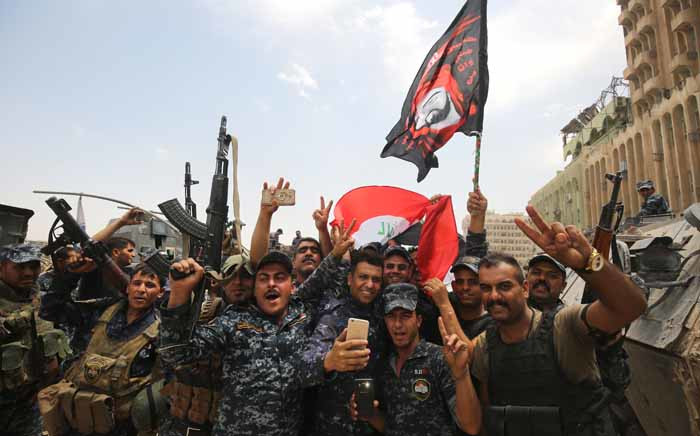 Members of the Iraqi federal police dance and wave their country's national flag in celebration in the Old City of Mosul on 8 July 2017. Picture: AFP.