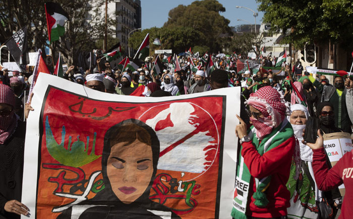 Demonstrators hold banners and wave Palestinian flags as they march through the city centre of Cape Town, South Africa, on 11 May 2021 to protest against Israeli attacks on Palestinians in Gaza. Picture: Rodger Bosch/AFP