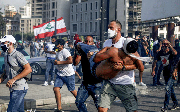 FILE: Lebanese basketball star Fadi al-Khatib carries a wounded demonstrator away from clashes in downtown Beirut on 8 August 2020, following a demonstration against a political leadership they blame for a monster explosion that killed more than 150 people and disfigured the capital Beirut. Picture: AFP
