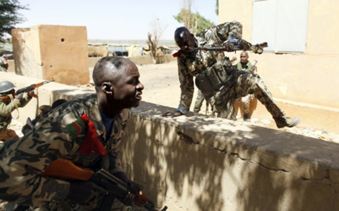 Malian soldiers take cover as they fight while clashes erupted in the city of Gao and an apparent car bomb struck near a camp housing French troops. Picture: AFP.