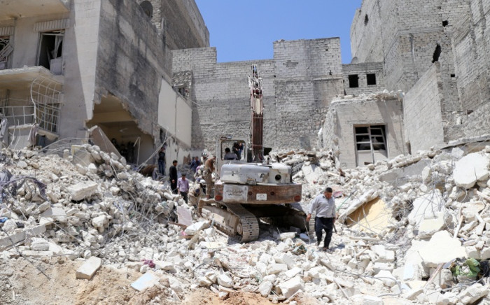 FILE: People inspect the rubble of collapsed buildings following a reported airstrike by government forces in 2015.Picture: AFP.