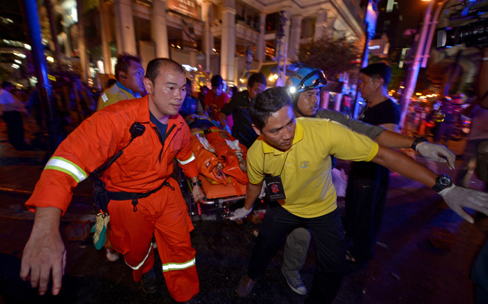 Thai rescue workers carry an injured person after a bomb exploded outside a religious shrine in central Bangkok late on 17 August, 2015 killing at least 10 people and wounding scores more. Picture: AFP.