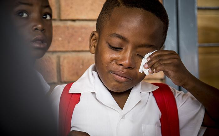 Grade 2 pupil Siyabonga Ambrose Mankgane wipes away tears on his first day back to school at the newly opened Nomzamo Madikizela Mandela Primary School in Soweto on 11 January 2017. Picture: Reinart Toerien/EWN.