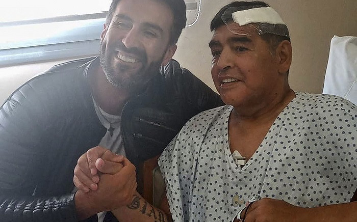 This handout photo released by the press officer of Diego Armando Maradona shows Argentine football legend Diego Maradona (R) shaking hands with his doctor Leopoldo Luque in Olivos, Buenos Aires province, Argentina, on November 11, 2020. Picture: AFP