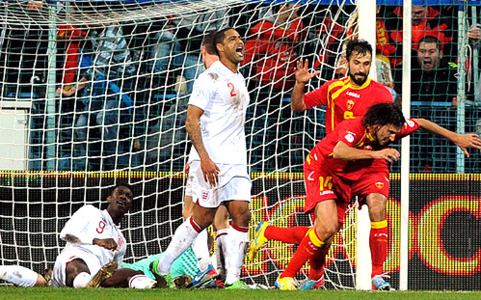 Montenegro players celebrate scoring a later equalising goal against England. England's Danny Welbeck and Glenn Johnson (standing) show their disappointment. Picture: AFP