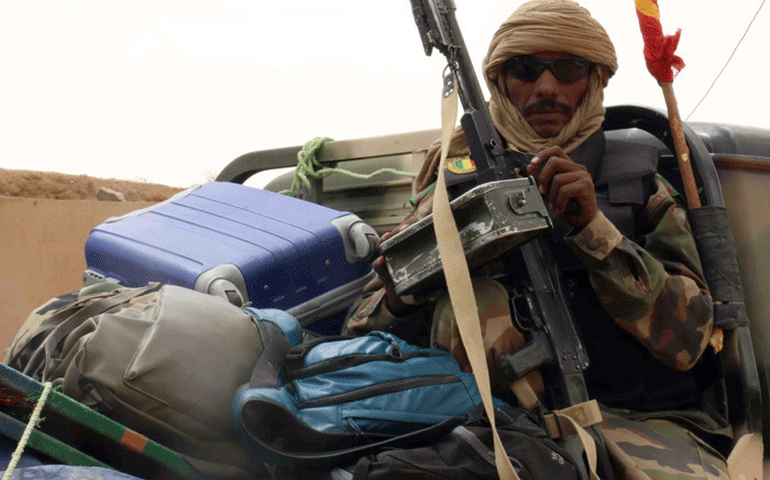 FILE: An armed Malian military man sits on the back of a truck on 17 May 2014 after around 30 civilians and soldiers went missing following clashes between separatist militants and the Malian army in the rebel-controlled northern city of Kidal. Picture: AFP.