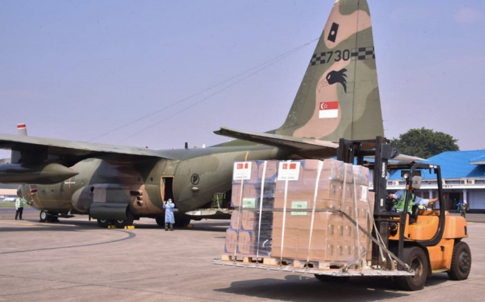 This handout picture taken and released on July 9, 2021 by the Indonesian military shows officers unloading medical equipment, such as oxygen cylinders, ventilators as well as masks, gloves and gowns on two Singapore air force planes, to be used in the COVID-19 coronavirus pandemic, at the air force base in Jakarta. Picture: AFP.