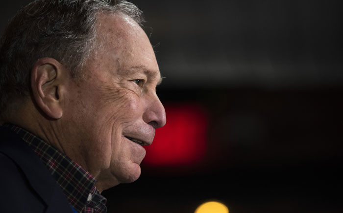 Democratic presidential candidate Mike Bloomberg has an aide take his daily briefings binder before speaking to supporters at the Viva Villa restaurant in San Antonio, Texas on 11 January 2020. Picture: AFP