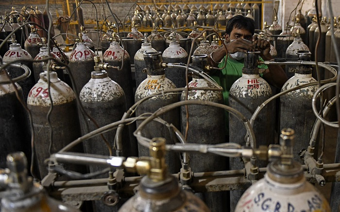 Workers are seen sorting oxygen cylinders that are being used for Covid-19 coronavirus patients before dispatching them to hospitals at a facility on the outskirts of Amritsar on April 28, 2021. Picture: Narinder Nanu / AFP.