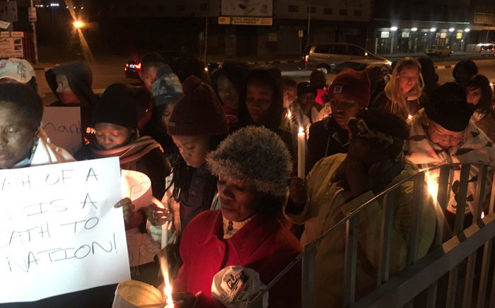 Women holding candles outside Booysens station -they're demanding police accountability when victims report crimes. Picture: Katleho Sekhotho/EWN