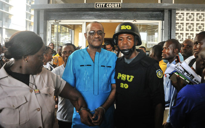 Former deputy governor of the Central Bank of Liberia Charles Sirleaf (C), the son of Liberia's former President Ellen Johnson Sirleaf, is escorted outside the City Court of Monrovia on 4 March 2019, where he appeared in court and charged with economic sabotage following a probe into missing banknotes. Picture: AFP