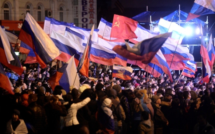 Pro-Russian Crimeans wave Russian flags as they gather to celebrate in Simferopol's Lenin Square on March 16, 2014 after exit polls showed that about 93 percent of voters in Ukraine's Crimea region supported union with Russia. Picture: AFP.