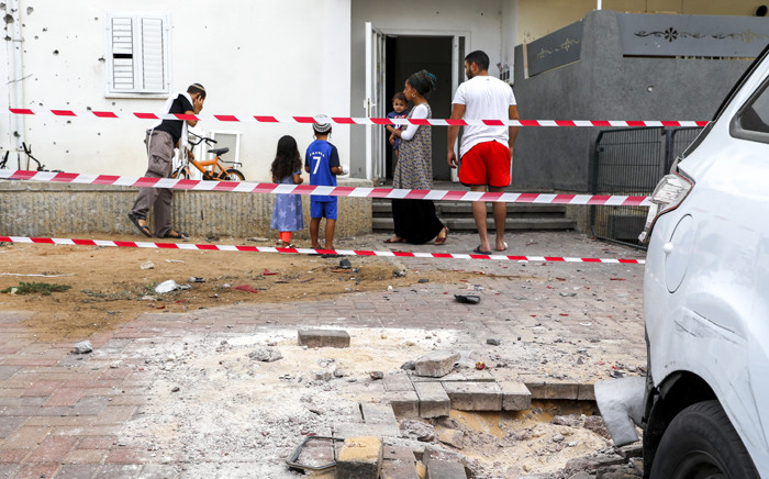 Israelis stand and inspect surrounding damages outside the cordoned area where a rocket fired by militants from the Gaza Strip fell and created a small crater in the southern Israeli town of Sderot on 9 August 2018.  Picture: AFP.