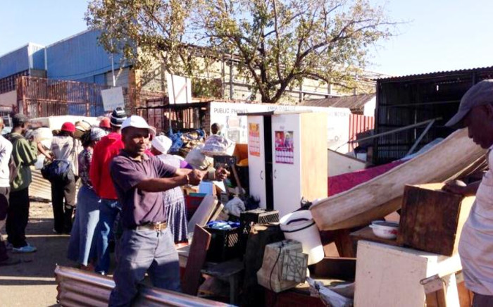 Evicted Alexandra residents rummage through a pile of their belongings, 4 June 2014. Picture: Lesego Ngobeni/EWN.