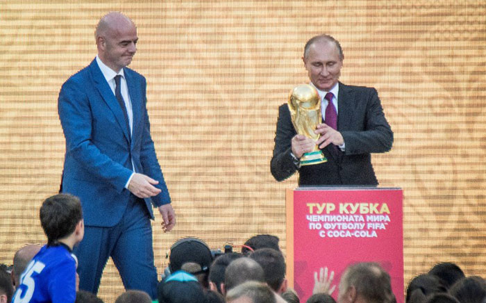 Russian President Vladimir Putin (R) holds the FIFA World Cup Trophy flanked by FIFA President Gianni Infantino (L) during the opening of the trophy tour ceremony at Luzhniki stadium in Moscow on September 9, 2017. Picture: AFP.