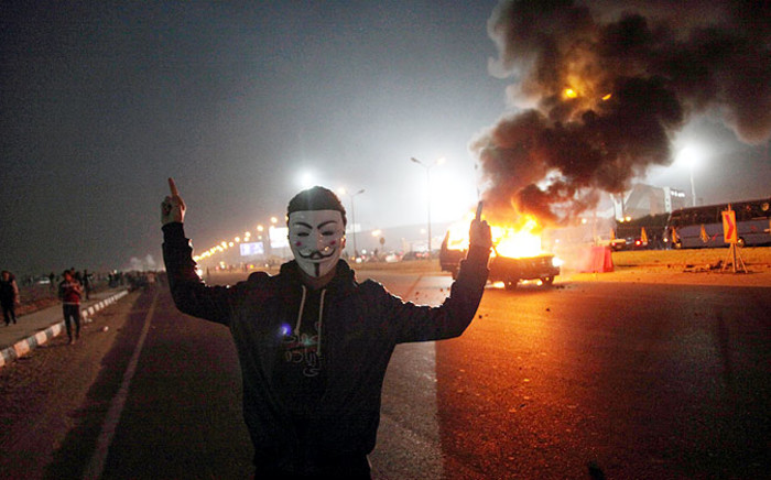 FILE: A man stands near a burning car outside a sports stadium in a Cairo's northeast district during clashes between supporters of Zamalek football club and security forces on 8 February 2015. 22 people were killed and several injured. Picture: AFP