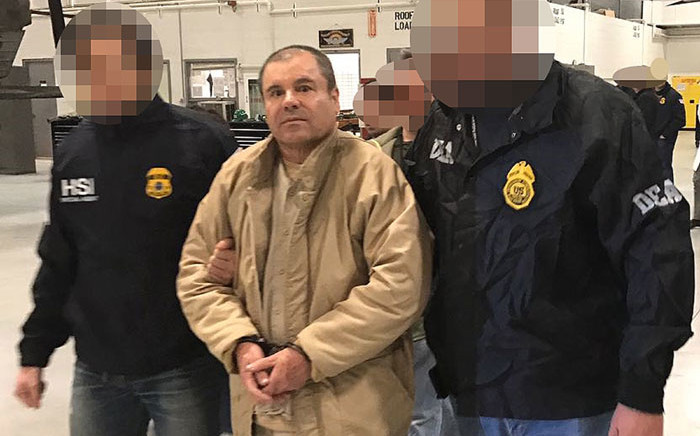 "FILE: A handout picture released by the Mexican Interior Ministry on 19 January 2017 shows Joaquin Guzman Loera aka ""El Chapo"" Guzman (C) escorted in Ciudad, Juarez by the Mexican police as he is extradited to the United States. Picture: AFP"