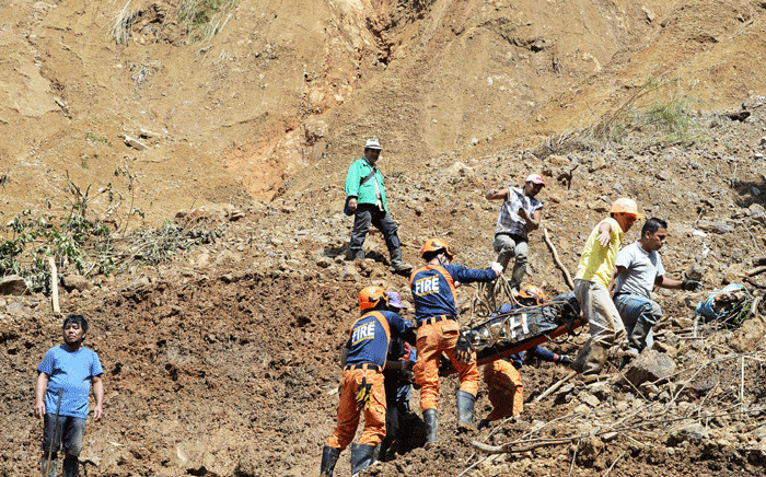 Rescuers carry a body bag containing a landslide victim, triggered by heavy rains during Typhoon Mangkhut, in Itogon, Benguet province on 18 September 2018. Picture: AFP.