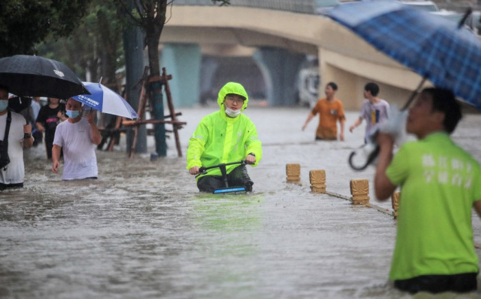 This photo taken on 20 July 2021 shows a man riding a bicycle through flood waters along a street following heavy rains in Zhengzhou in China's central Henan province. Picture: STR/AFP