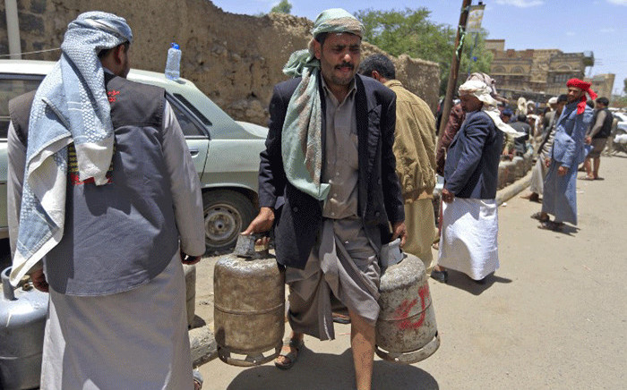 A Yemeni man carries gas cylinders after filling them up amid increasing shortages in the Yemeni capital Sanaa, on 2 September, 2018. Picture: AFP.