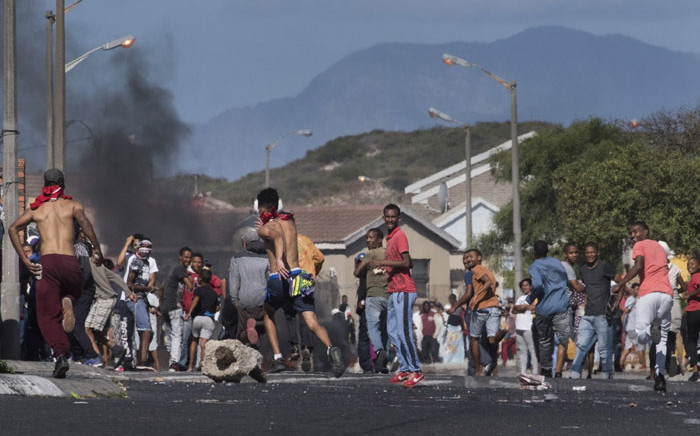 FILE: People run away as a South African Police Services armoured vehicle (not visible) approaches them during clashes with residents of Tafelsig, an impoverished suburb in Mitchells Plain, near Cape Town, on 14 April 2020, after some people in the community did not receive food parcels which were being handed out as part of the support for this community during the nation wide lockdown to curb the spread of the coronavirus. Picture: AFP