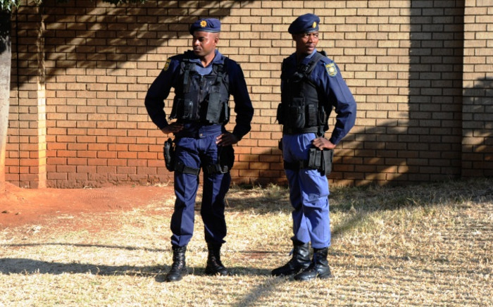 Policemen stand outside the Sophiatown Magistrates Court on 5 August 2014 ahead of the appearance of a man allegedly implicated in the shooting of Westbury toddler, Luke Tibbetts. Picture: Sapa.